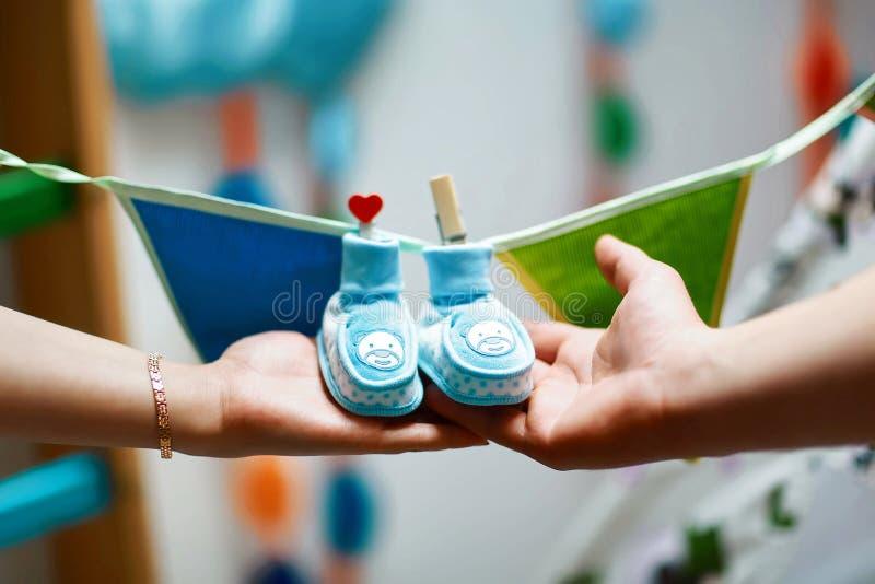 Butins nouveau-nés de bébé dans des mains de parents, ventre de femme enceinte, chaussures bleues accrochant sur une ficelle avec photos stock