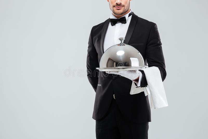 Butler dans le smoking et gants tenant le plateau argenté avec le couvercle photo stock