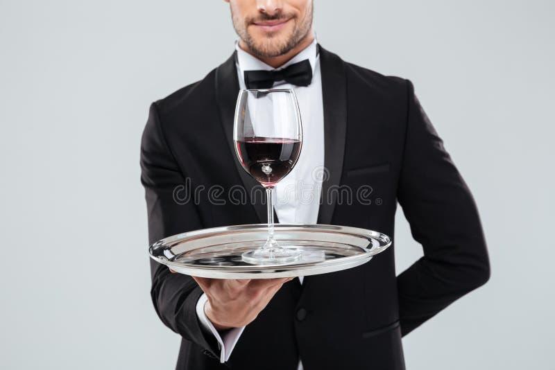 Butler dans le smoking tenant le plateau argenté avec le verre de vin image stock