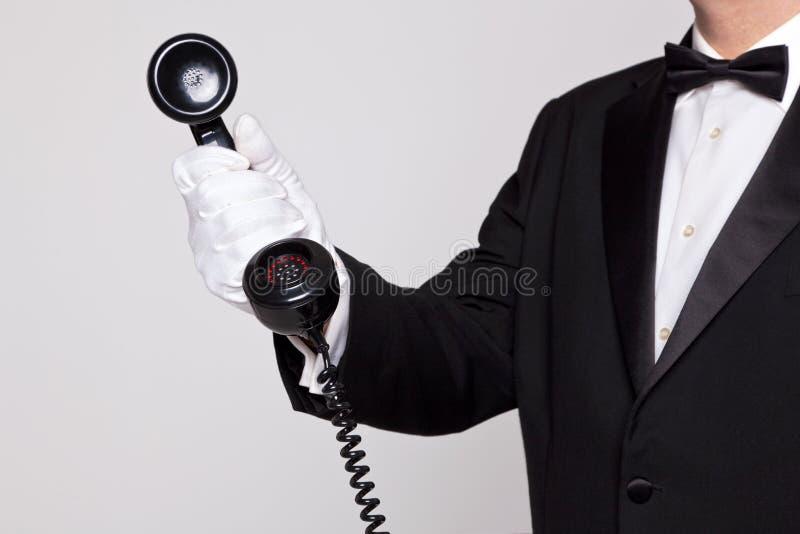 Butler, der einen Telefonhörer anhält stockbild