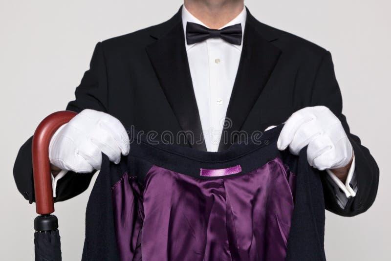 Butler die uw laag en paraplu houden. royalty-vrije stock afbeeldingen