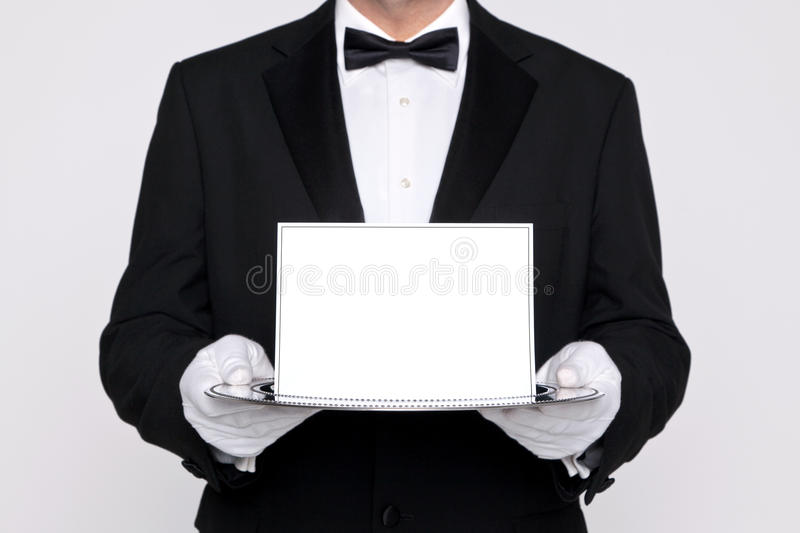 Butler holding a blank card upon a silver tray royalty free stock photo