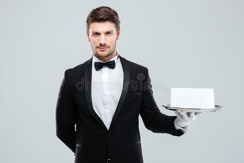 Butler im Smoking und Handschuhe, die Behälter mit leerer Karte halten stockfotografie