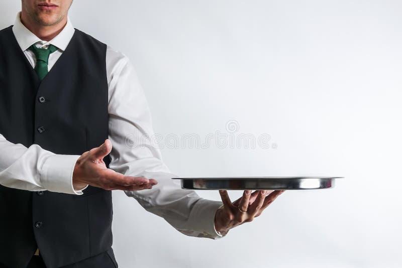 Butler/kelner in kostuumvest die een leeg zilveren dienblad dragen royalty-vrije stock afbeelding