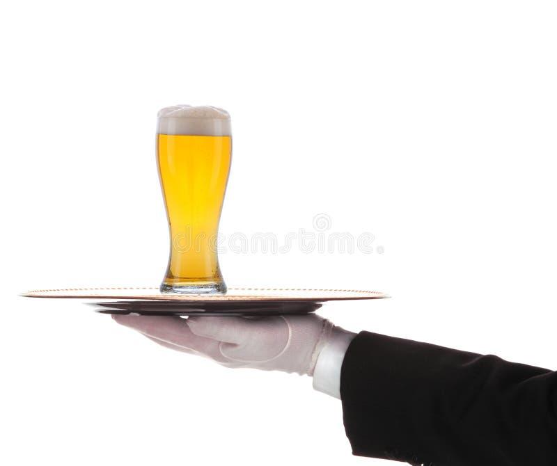 Butler met Bier en dienblad op uitgestrekt wapen stock fotografie