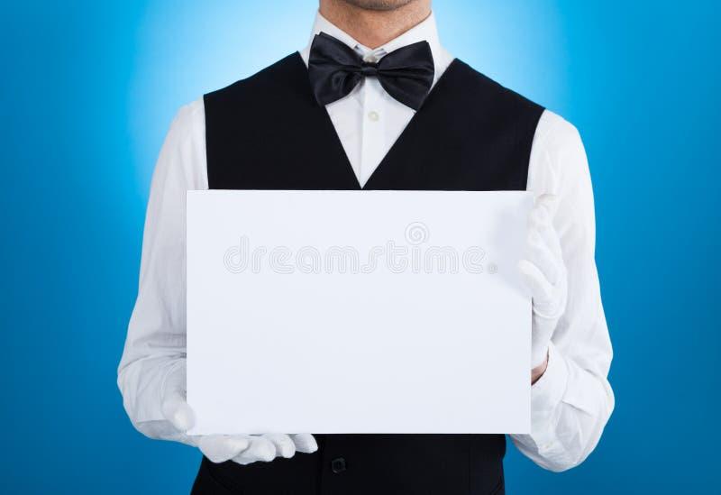 Butler tenant le panneau d'affichage vide photo libre de droits