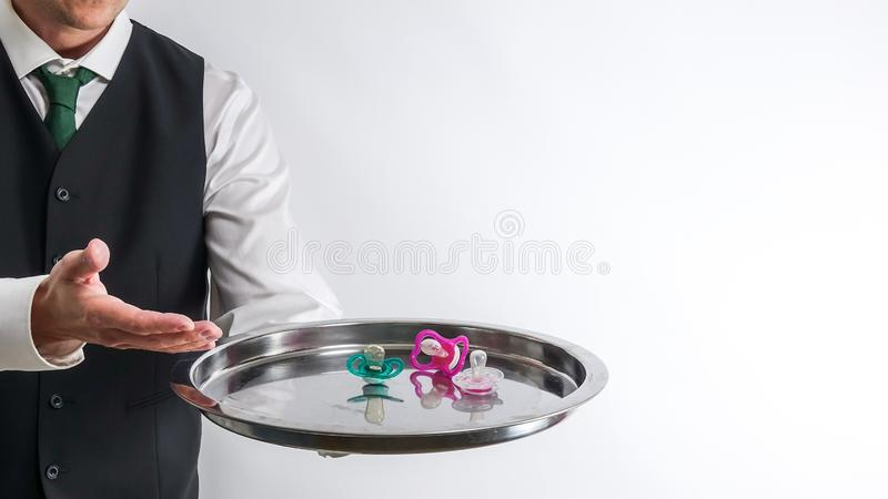 Butler / waiter holds a silver tray with pacifiers. Concept for spoiled children and overprotective parents. Blank white background with copy space for text royalty free stock photos