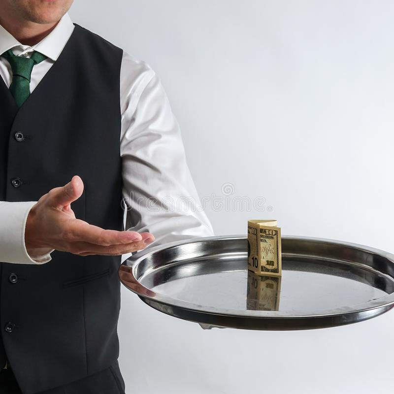 Butler / waiter holds a silver tray with a ten dollar bill. royalty free stock image
