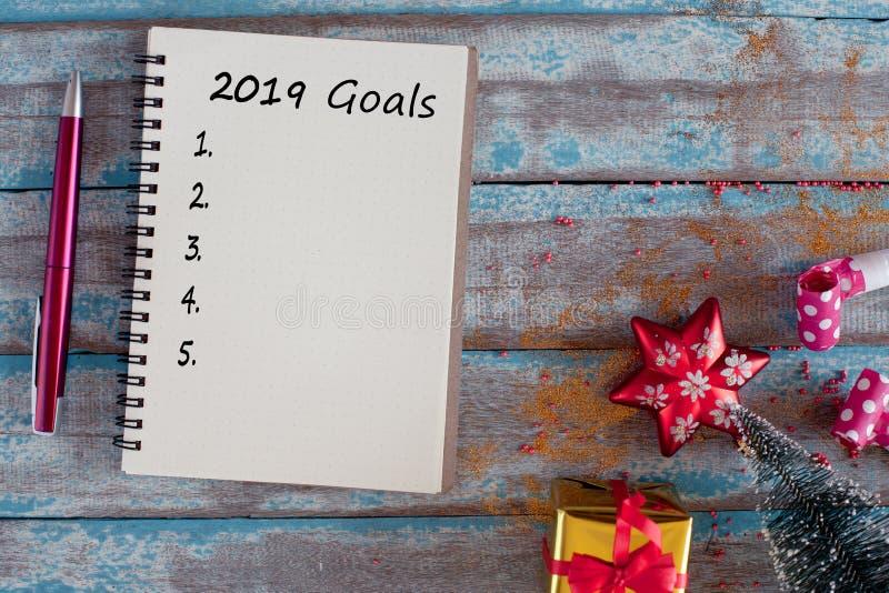 2019 buts énumèrent avec le carnet et le stylo sur le tabl en bois images libres de droits