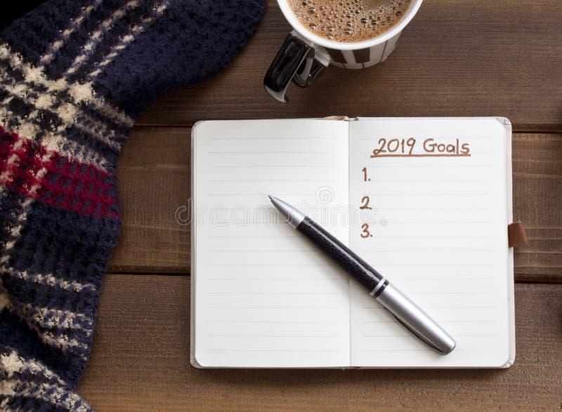 2019 buts énumèrent avec le carnet, tasse de café au-dessus de bureau en bois images libres de droits
