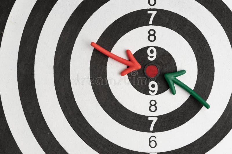Buts d'affaires ou flèche de cible, verte et rouge financière se dirigeant au centre rouge de point de la cible noire et blanche  photo stock