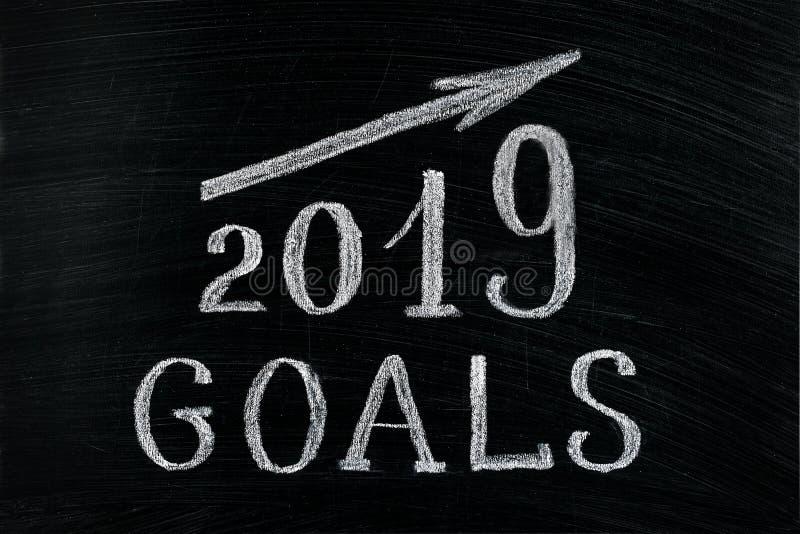 Buts de la nouvelle année 2019 avec une craie en hausse des textes de flèche sur un tableau noir Tableau écrit avec des buts des  image stock