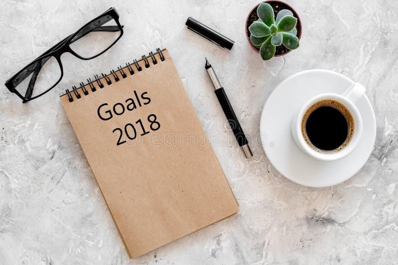 Buts de mots pour 2018 écrivant dans le carnet près des verres et de la tasse de café sur la maquette en pierre grise de vue supé photo stock