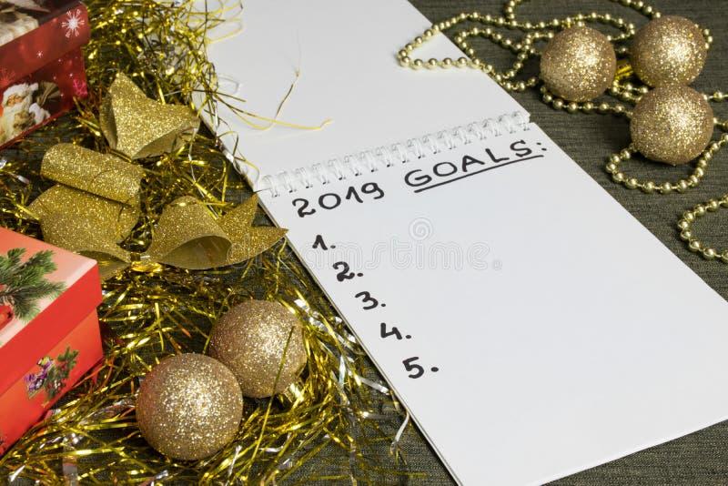 2019 buts de nouvelle année avec blanco l'espace dans le carnet entouré avec la décoration d'or et rouge images stock