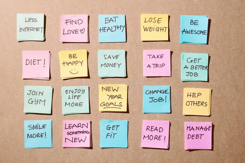 Buts de nouvelle année ou résolutions - notes collantes colorées sur un bloc-notes avec la tasse de café image libre de droits