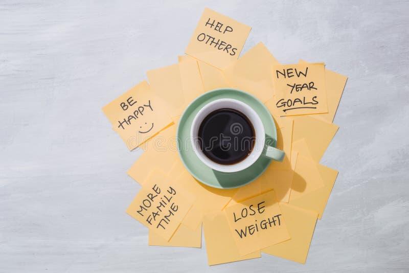 Buts de nouvelle année ou résolutions - notes collantes jaunes avec du café image stock