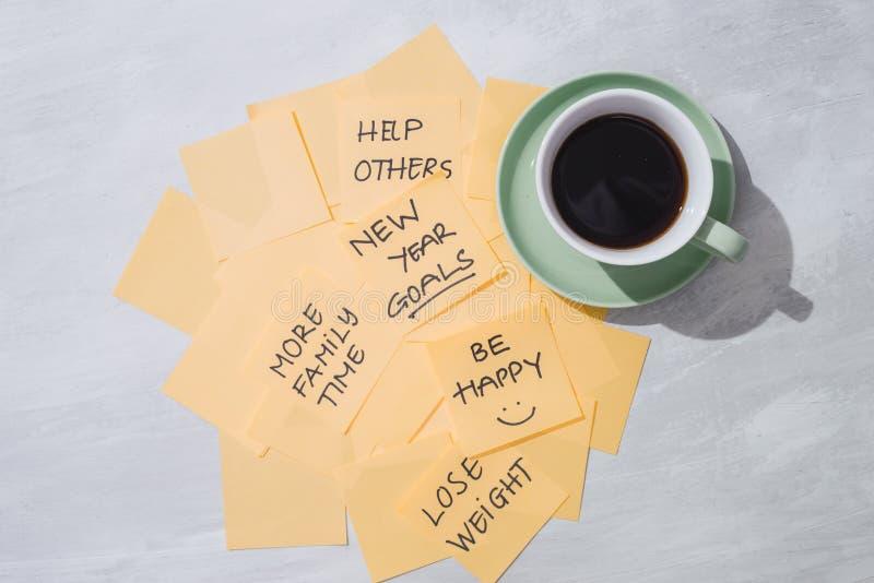 Buts de nouvelle année ou résolutions - notes collantes jaunes avec du café sur la table images libres de droits