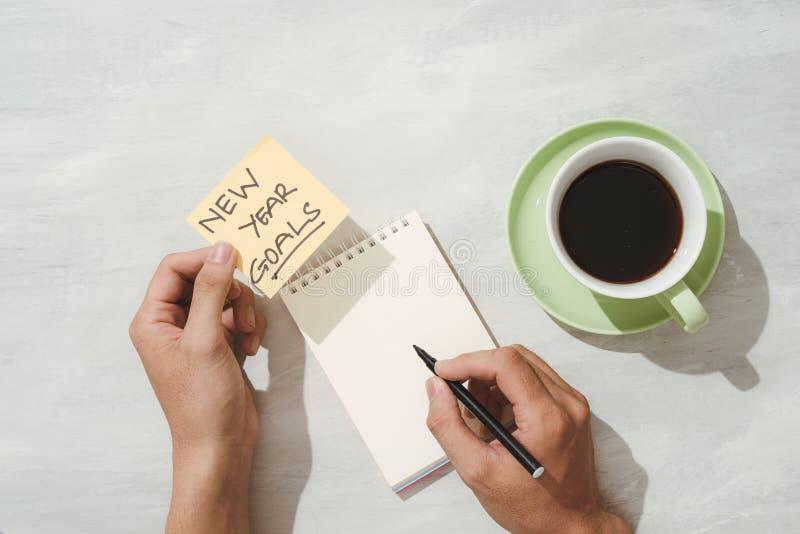 Buts de nouvelle année ou résolutions - notes collantes jaunes avec du café sur la table photographie stock libre de droits