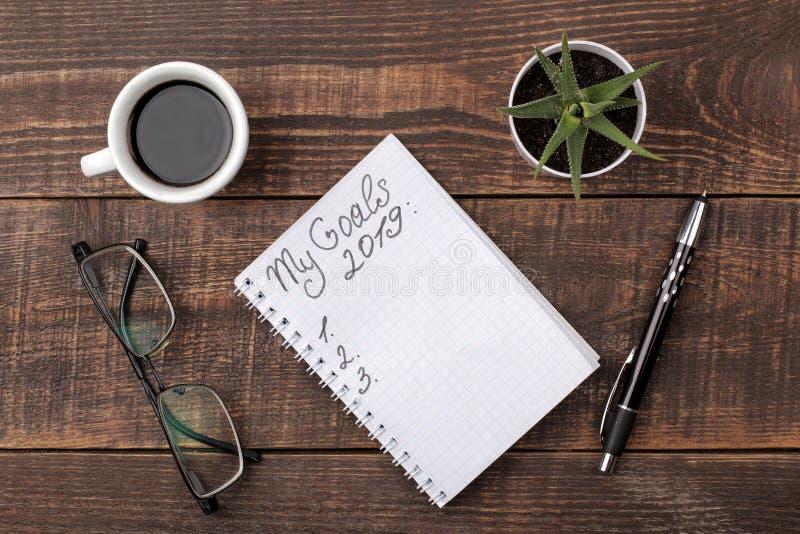 Buts pour 2019 texte dans le carnet avec le stylo, les verres et le café sur un fond en bois brun photos stock