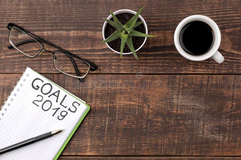 Buts pour 2019 texte dans le carnet avec le stylo, les verres et le café sur un fond en bois brun image stock