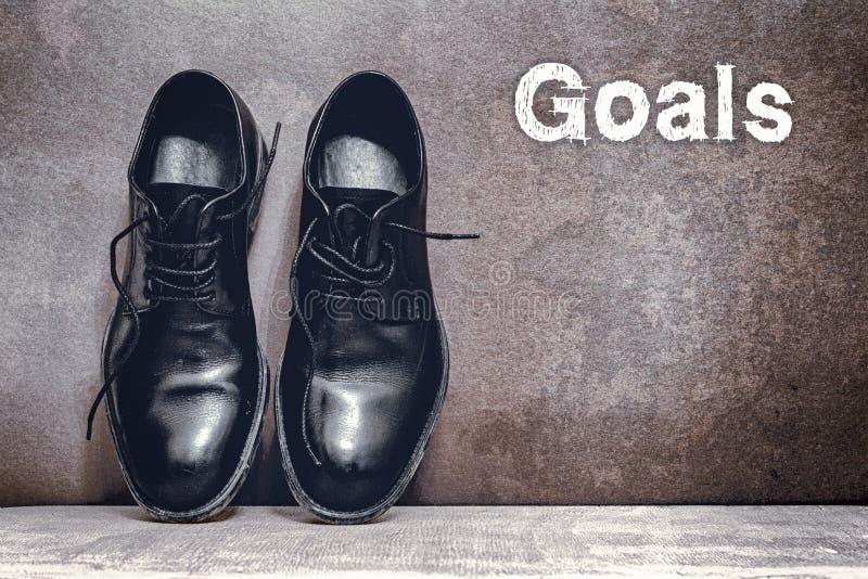 Buts sur les chaussures brunes de conseil et de travail sur le plancher en bois images stock