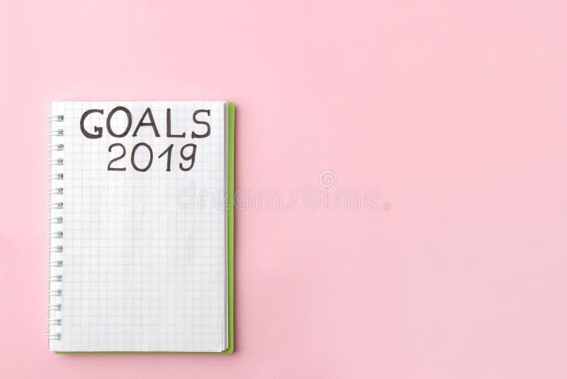 Buts 2019 texte dans un carnet sur un fond rose lumineux Vue de ci-avant Avec l'espace pour le texte photo libre de droits