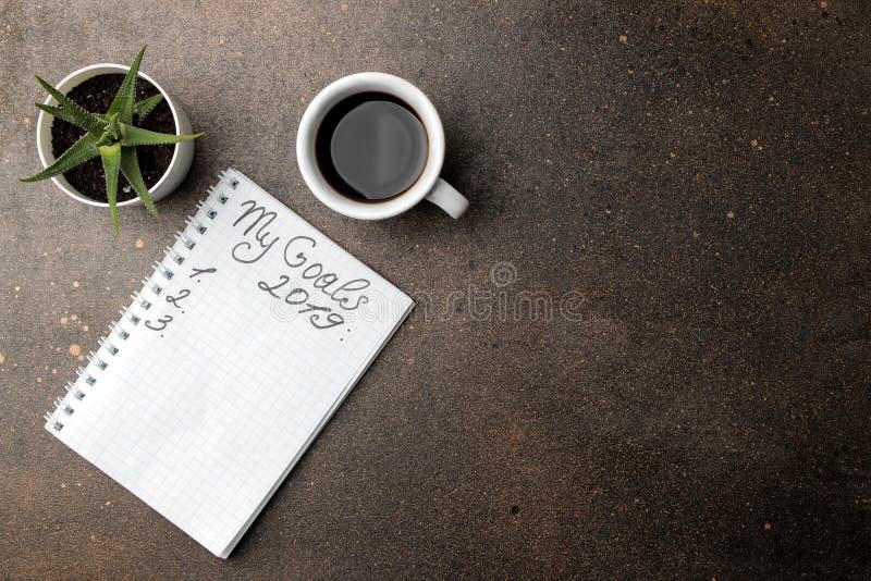Buts 2019 texte en carnet, café et fleur sur un fond foncé image libre de droits