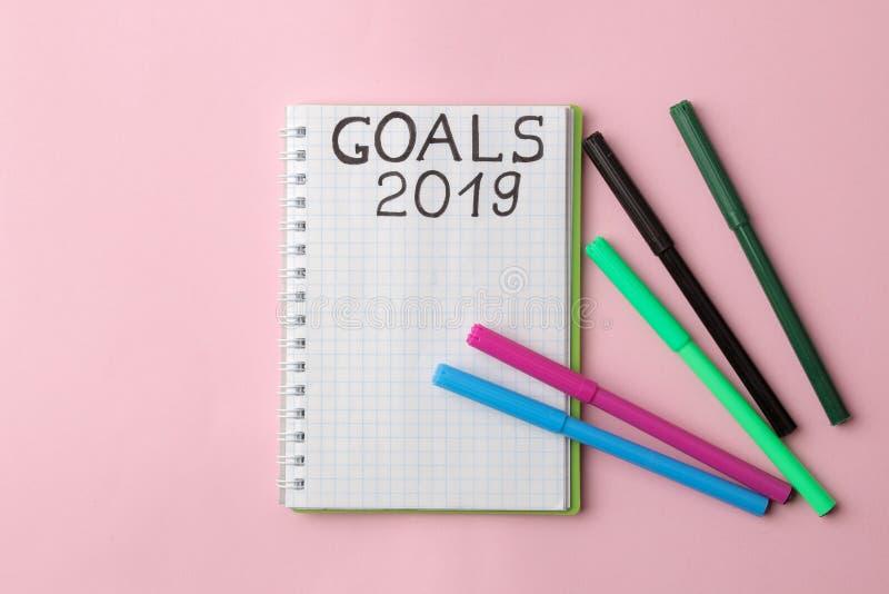 Buts 2019 texte sur un bloc-notes avec les stylos feutres colorés sur un fond rose lumineux photographie stock