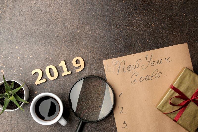 Buts 2019 texte sur un morceau de papier avec du café, une loupe et un cadeau sur un fond foncé images stock