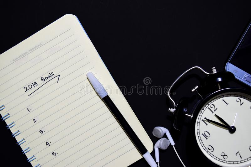 2019 buts textotent sur le carnet, réveil, le stylo de couleur, écouteur sur le fond noir images stock