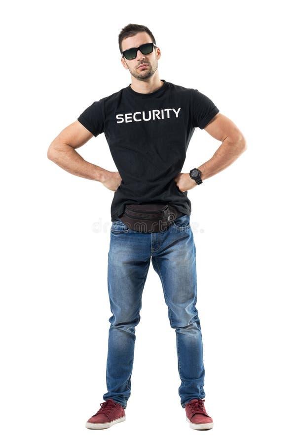 Buttafuori macho seri o ufficiale clandestino con le mani sulle anche che esaminano macchina fotografica fotografia stock libera da diritti