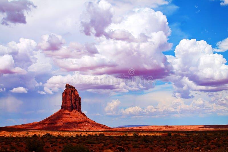 Butte de rotsvorming van grondniveau met schrobt struiken en pluizige wolken in Monumentenvallei, Arizona stock afbeelding