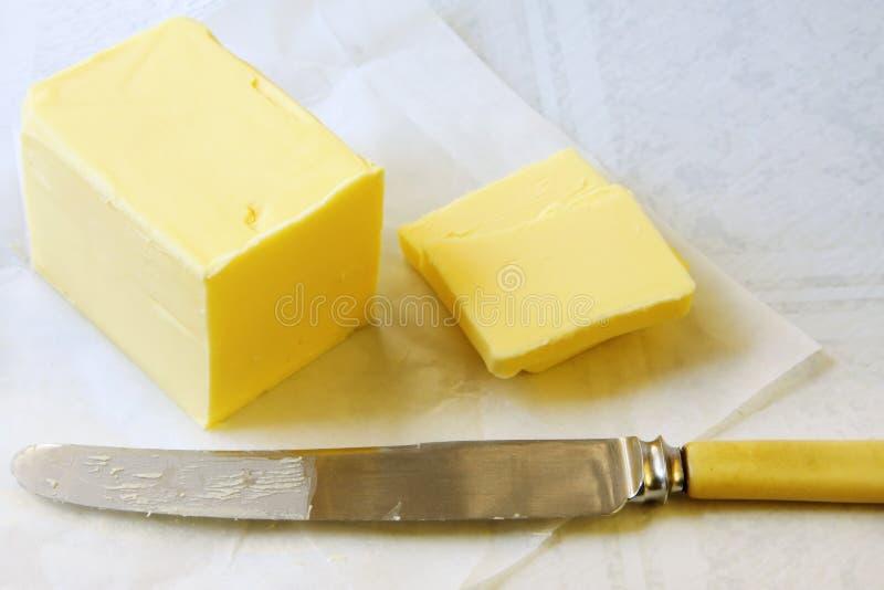 Butter. Block of golden butter, sliced with a bone-handled vintage knife stock images