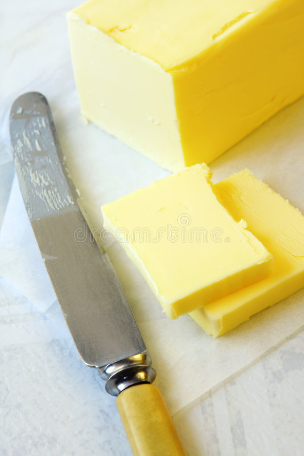 Butter. Block of butter, cut with bone-handled vintage knife royalty free stock image