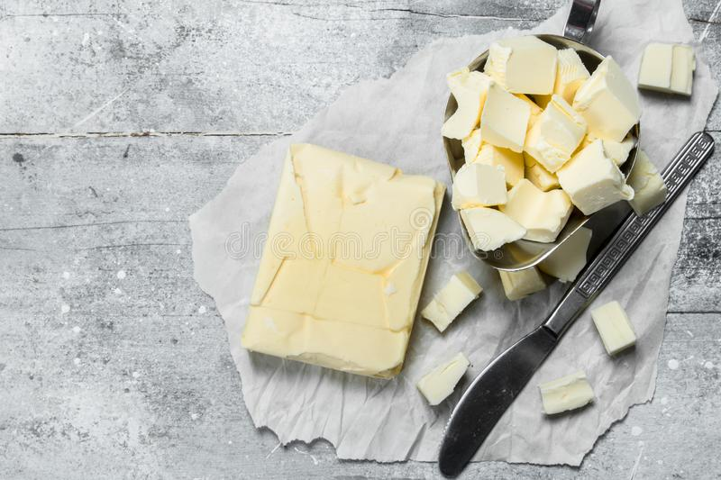 Butter in a bowl with a knife. On a rustic background royalty free stock photography
