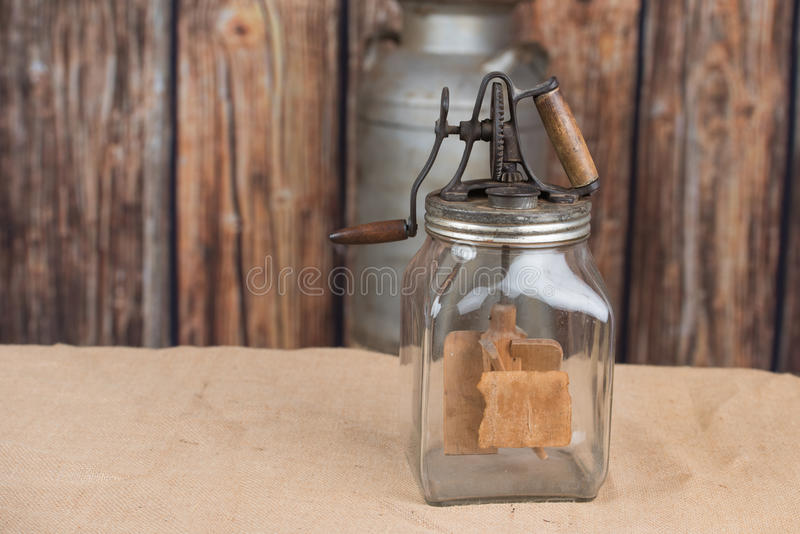 Butter churn. Antique butter churn sits on a burlap cover with wooden background. Old milk can is in the background royalty free stock photo