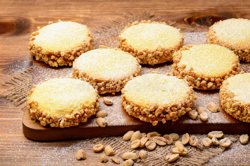 Butter cookies (alfajores) with caramel and peanut on wooden background. royalty free stock image