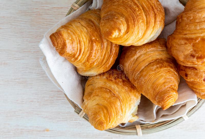 Butter croissants in small wicker basket. Aerial top view on c. Lear wood background stock photos