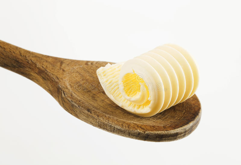 Butter curl on a wooden spoon stock photo