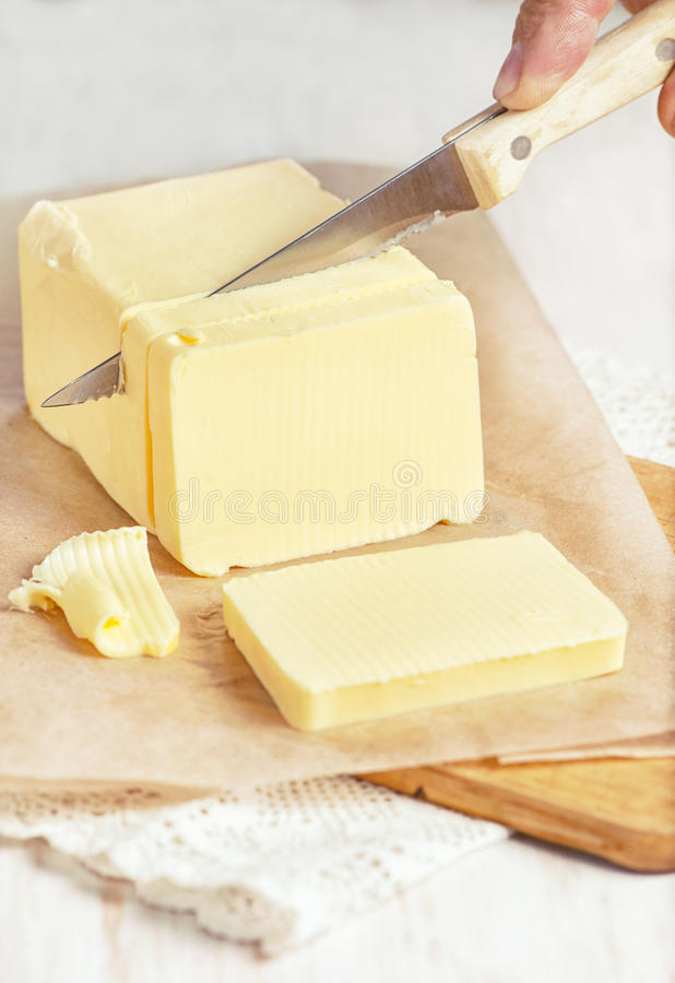 Butter cutting by knife. Piece of butter on paper cutting by knife stock photo