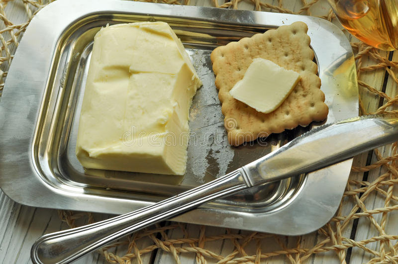 A butter dish with fresh butter, a biscuits with butter spread on it and a knife stock photography