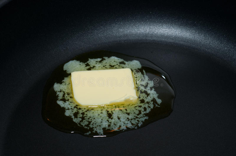 Butter in a hot pan. Butte is melting from the heat of a pan stock image