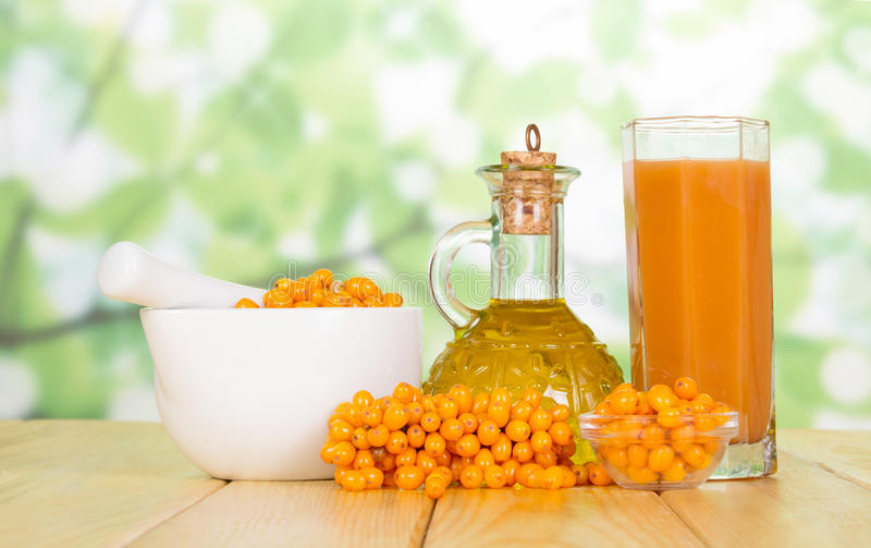 Butter, juice, and fresh sea buckthorn on the table stock images