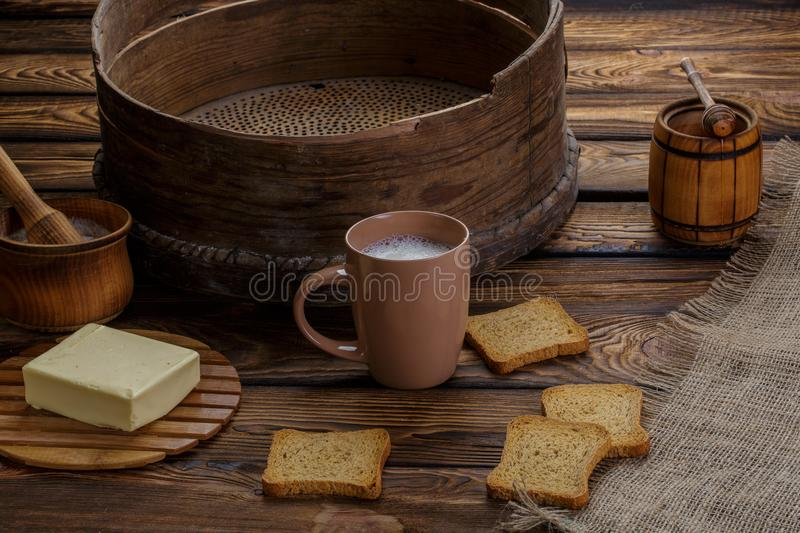 Butter toast, honey and milk on wood backgraund. Butter toast, honey and cup with milk , flour, butter, on wood backgraund. Around the ingredients of the sieve stock image