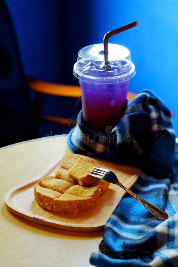 Butter toasted bread on wood trey and ice sour purple butterfly pea juice blue table wood table set stock photography