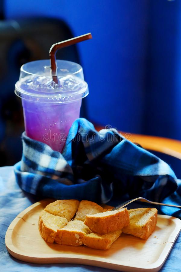 Butter toasted bread on wood trey and ice sour purple butterfly pea juice blue table wood table set stock photos