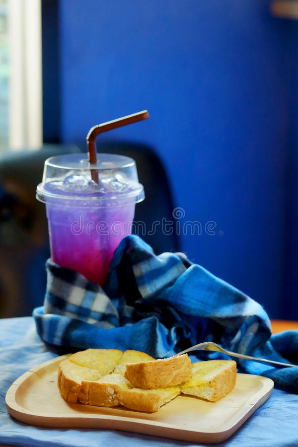 Butter toasted bread on wood trey and ice sour purple butterfly pea juice blue table wood table set stock image