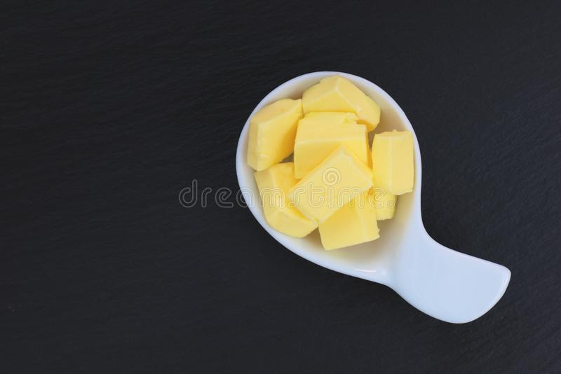 Butter in white cup on black slate plate. With copy space royalty free stock photo