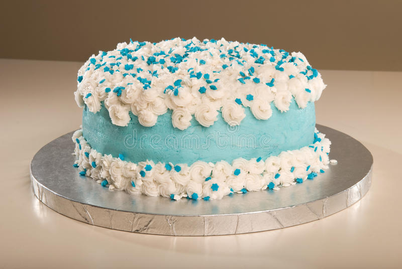 Buttercreme Cloud Cake. A fancy butter-creme decorated cake with blue and white sprinkles on a silver cake board royalty free stock photo