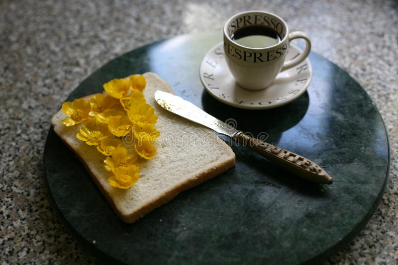 Buttercups and bread with your expresso?. A lighthearted look at breakfast, using buttercups instead of butter on a slice of white bread. A knife with butter royalty free stock image